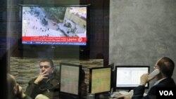 Para investor di bursa saham Amman, Yordania mengikuti perkembangan politik di Mesir melalui televisi.