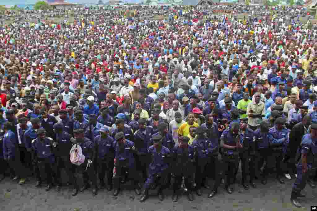 Congo government policemen, foreground, and civilians gather during a M23 rally in Goma, Congo, November 21, 2012.