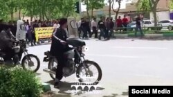 FILE - In this frame from a social media video posted April 13, 2018, people in Khorasgan, Iran, march to protest water shortages that are hurting local farmers.