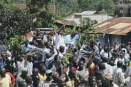 Leader of the opposition party Forum for Democratic Change Kizza Besigye, background center right, beside his wife Winnie Byayima, left, waves to large crowds of supporters as he returns from Nairobi after medical treatment, May 12, 2011