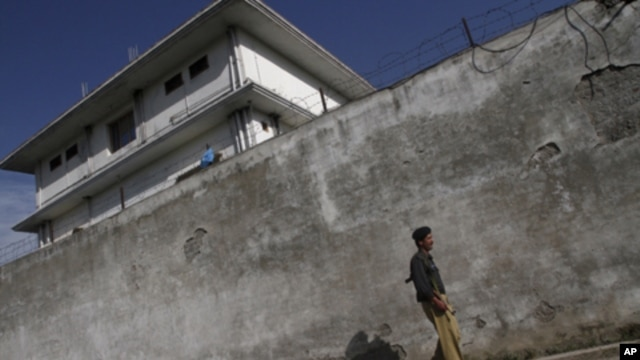 A policeman walks in front of the compound where Osama bin Laden was killed in Abbottabad, Pakistan, May 3, 2011.