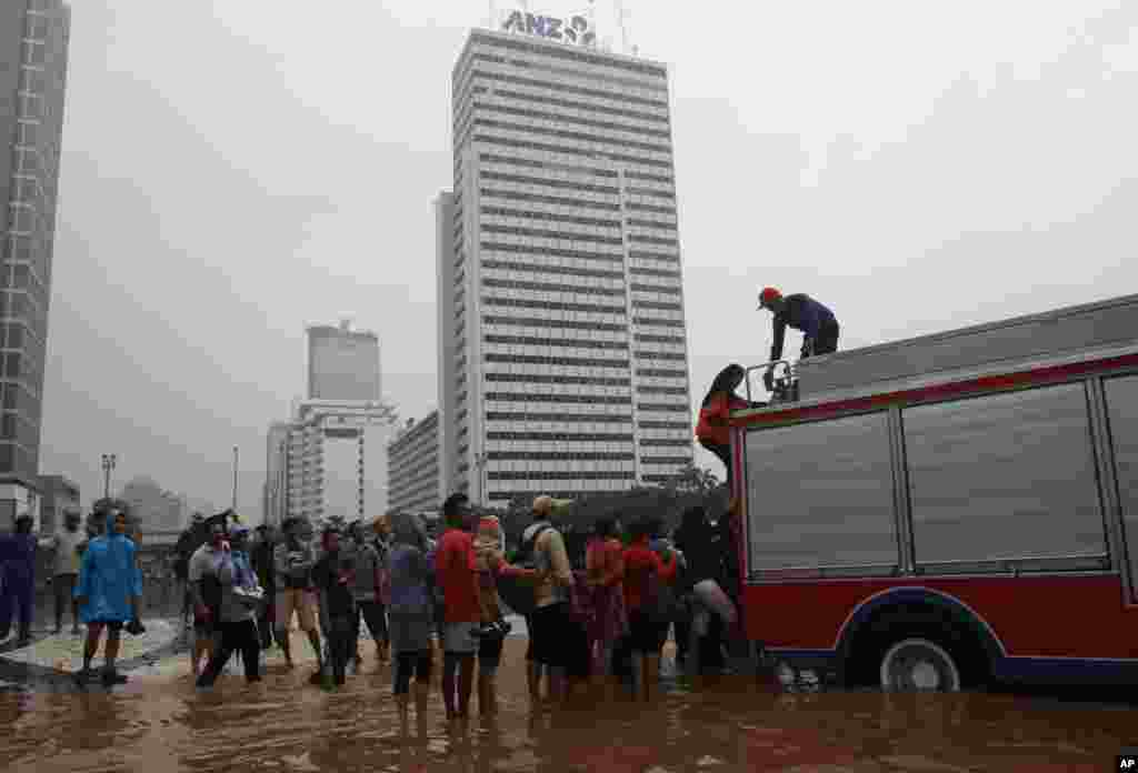 Indonesian firefighters help people in a flooded street in Jakarta, Indonesia, January 17, 2013.