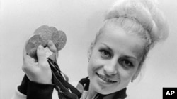 FILE - In this Oct., 1968, file photo, Vera Caslavska of Czechoslovakia holds her four Olympic medals, three gold and one silver which she won in the gymnastics competition.