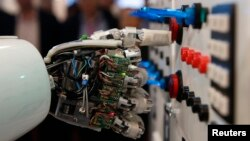 FILE - The hand of humanoid robot AILA (artificial intelligence lightweight android) operates a switchboard during a demonstration at the CeBit computer fair in Hanover, March, 5, 2013.