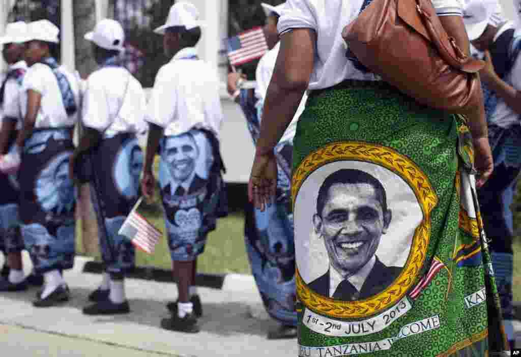 """Gabdho dhalinyaro ah iyo haween xiran guntiinooyinka hiddaha iyo dhaqanka oo lagu magacaabo """"Khanjas"""" uuna ku sawiran yahay Madaxweyne Obama oo safan aqalka madaxtooyada ee magaalada Dar es Salaam, Tanzania, July 1, 2013."""