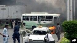 بارہ مئی 2007ء کا ایک منظر جس میں بعض شرپسند گاڑیوں کو آگ لگانے کے بعد ایک گاڑی کو توڑ پھوڑ رہے ہیں۔ (فائل فوٹو)