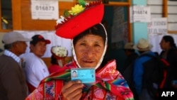 Una mujer muestra su documento de identidad en una mesa electoral en Ollantaytambo, en la provincia de Urubamba, región de Cusco, mientras el país vota sobre las reformas constitucionales el 9 de diciembre de 2018.