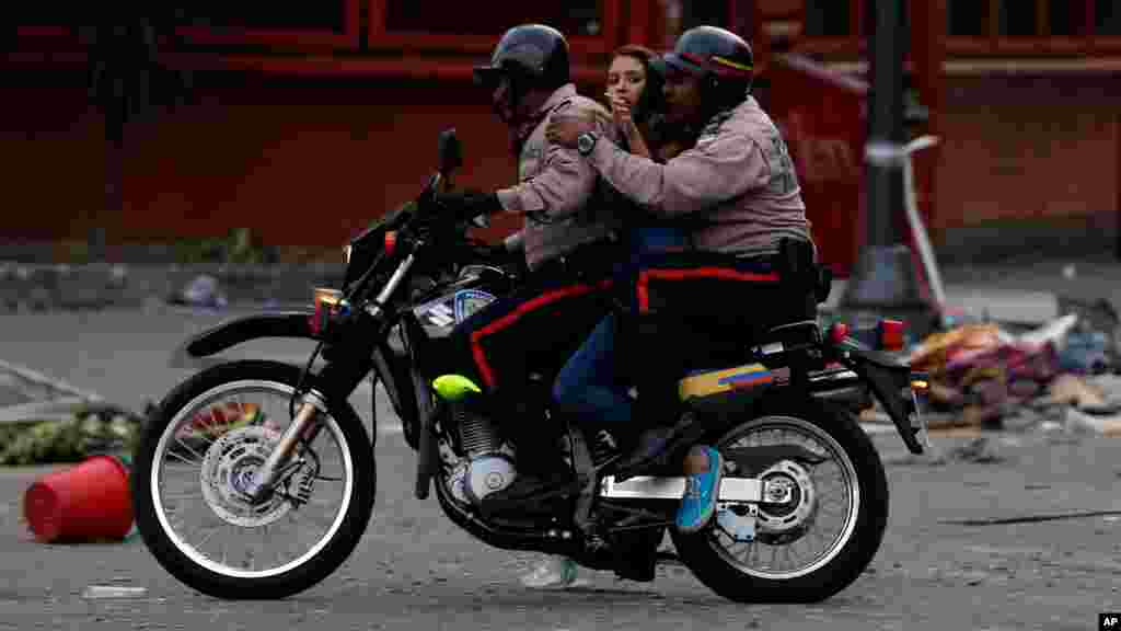 Motorizados de la policía se llevan a una manifestante arrestada.