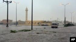 FILE - In this Nov. 24, 2015 image released by the Saudi Press Agency, SPA, a car drives on a flooded street in Al-Qassim Region, west of Riyadh, Saudi Arabia.