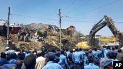 Police officers secure the perimeter at the scene of a garbage landslide, as excavators aid rescue efforts, on the outskirts of the capital Addis Ababa, Ethiopia, March 12, 2017.