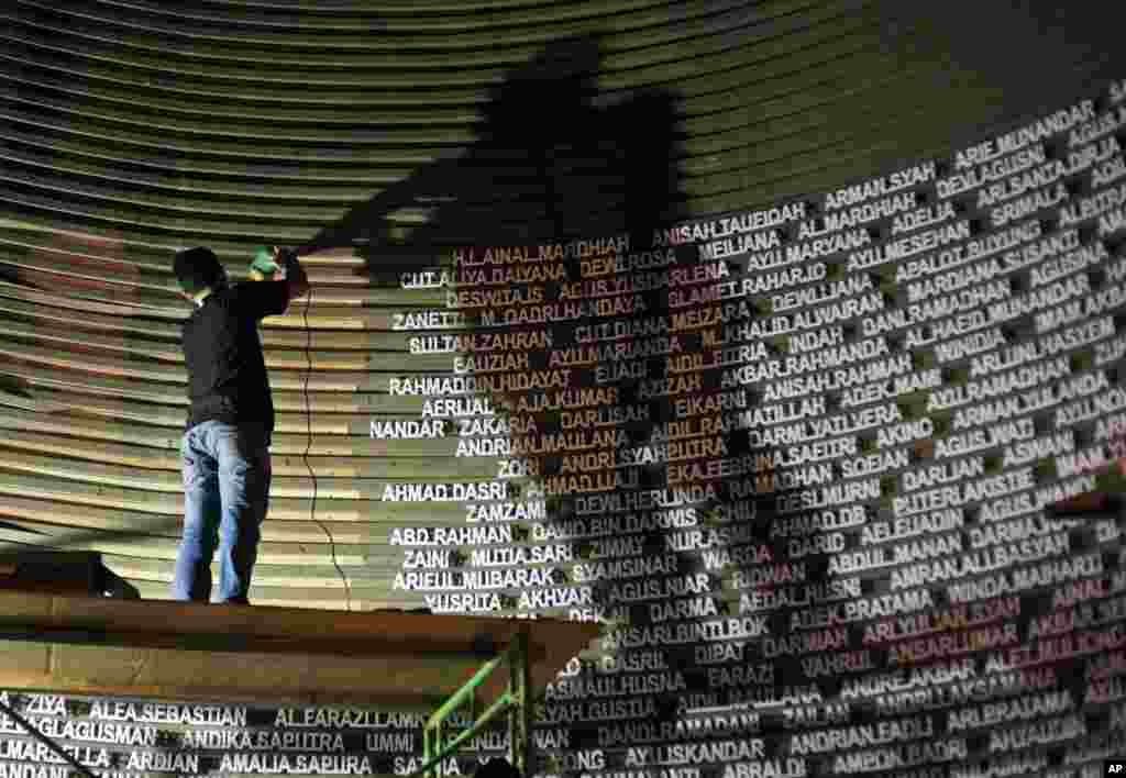 A worker installs the names of the victims of the 2004 Indian Ocean tsunami on the wall of the Tsunami Museum ahead of the 10th anniversary of the killer waves in Banda Aceh, Aceh province, Indonesia.