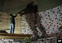 FILE - A worker installs the names of the victims of the 2004 Indian Ocean tsunami on the wall of the Tsunami Museum ahead of the 10th anniversary of the killer waves in Banda Aceh, Aceh province, Indonesia, Dec. 4, 2014.