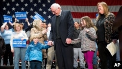 Democratic presidential candidate Sen. Bernie Sanders of Vermont, center, is joined by his wife Jane, right, and grandchildren, Dylan, 4, and Ella, 7, at a town hall at the Orpheum Theater in Sioux City, Iowa, Jan. 19, 2016. (AP Photo/Andrew Harnik)