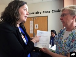 FILE - In this May 2, 2017 photo, Patsy Stinchfield, left, senior director of infection control at Children's Minnesota in Minneapolis, talks with nurse Kathy Kaul about a measles screening questionnaire that hospital staff are using to assess a patient's