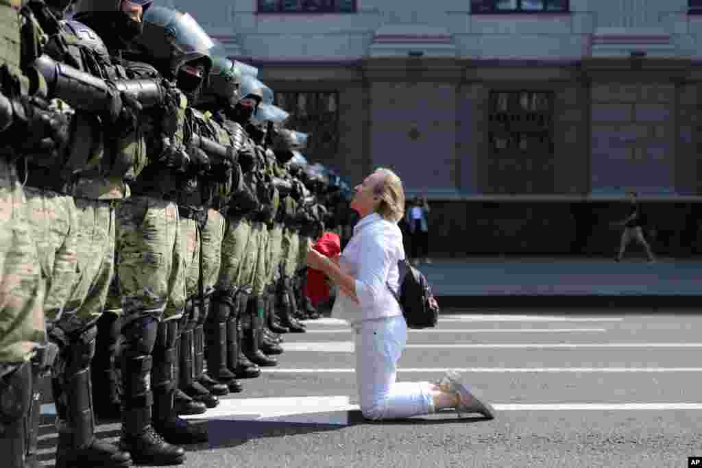A woman kneels in front of a riot police line as they block Belarusian opposition supporters rally in the center of Minsk, Belarus.