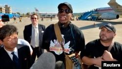 Dennis Rodman (C) llega al aeropuerto de Pyongyang, Corea del Norte, en su segunda visita este año a ese país.