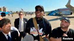 Mantan bintang basket Amerika, Dennis Rodman (tengah) tiba di bandara Pyongyang, Korea Utara, untuk kunjungan 'diplomasi bola basket' (3/9).