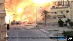 FILE - This photo posted on a file-sharing website Jan. 11, 2017, by the Islamic State Group in Sinai, a militant organization, shows an explosion as militants attack an Egyptian police checkpoint, Jan. 9, 2017, in el-Arish, north Sinai, Egypt.