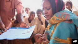 Sudanese women receives information about childhood immunizations.