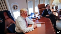 President Donald Trump, with his Chief of Staff Reince Priebus, sits at his desk on Air Force One upon their arrival at Andrews Air Force Base, Jan. 26, 2017.