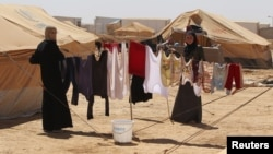 Syrian refugees hang clothes at Al Zaatri refugee camp in the Jordanian city of Mafraq, near the border with Syria, September 2, 2012.
