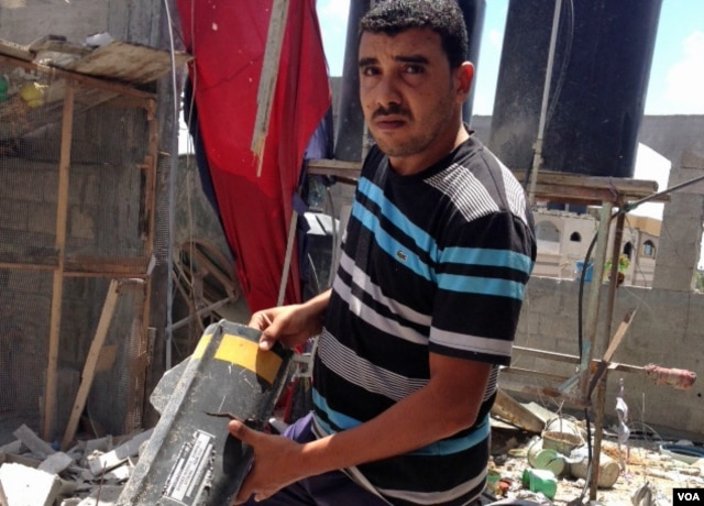 Anwar Mohammed holds part of a rocket that destroyed his family's home in Gaza during Israel's Operation Protective Edge targeting Palestinian militants. (VOA / Gabe Joselow)