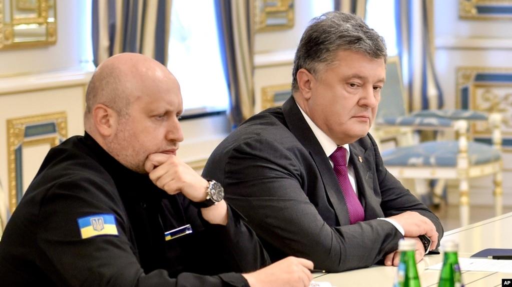 Presiden Ukraina Petro Poroshenko (kanan) dan Kepala Dewan Pertahanan dan Keamanan Ukraina Oleksandr Turchynov berbincang di sesi dewan tersebut di Kiev, Ukraina Kamis (11/8).