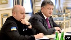 FILE - Ukraine's President Petro Poroshenko, right, and Oleksandr Turchynov, Chairman of Ukraine's National Security and Defense Council, chair a council meeting in Kyiv, Ukraine, Aug. 11, 2016. Both Poroshenko and Turchynov have made cybersecurity a strategic priority.