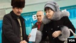 Warga Kazakhstan memasukkan kertas suaranya di pusat kota Almaty (15/1).
