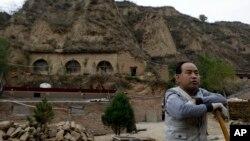 2012年10月18日,一个农民站在习近平青年时期在中国陕西省梁家河住过的窑洞附近。