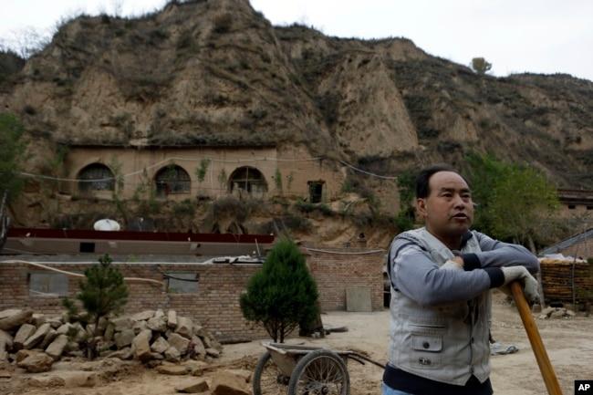2012年10月18日,一個農民站在習近平青年時期在中國陝西省梁家河住過的窯洞附近。
