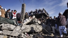 Local residents stand over the rubble of a damaged market caused by Saturday's bombing in Quetta, Pakistan on February 17, 2013.