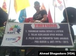 Seorang peserta unjuk rasa di depan Kedutaan Besar Amerika Serikat di Jakarta, dengan membawa spanduk yang menyuarakan tuntutan mereka terhadap pemerintah AS, 8 Oktober 2018. (Foto: VOA/ Ahmad Bhagaskoro)
