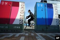 Seorang pria mengendarai sepeda dengan mengenakan masker melewati beberapa iklan Olimpiade dan Paralimpiade Tokyo 2020 di Tokyo, Senin, 12 April 2021. (Foto AP / Eugene Hoshiko)