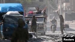 Les forces démocratiques syriennes (SDF) évacuent des civils dans le quartier de Manbij, à Alep, Syrie, le 12 août 2016.