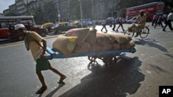 A man pulls a hand-drawn cart loaded with sacks of chickpeas on a main road in Mumbai, April 21, 2011