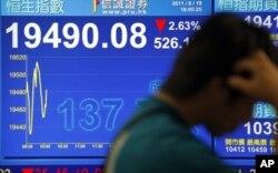 一位香港市民行經股市指數報告版前