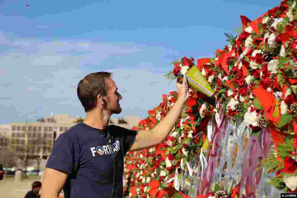 "Teleflora's ""Wall of Love,"" a custom, 50-foot wide, 8-foot high floral wall, is located in front of the Capitol building reflecting pool in Washington, Nov. 29, 2017. Teleflora invited the public to take one of the 1,000 handmade bouquets and give it to a family member, friend, loved one or someone they barely know."
