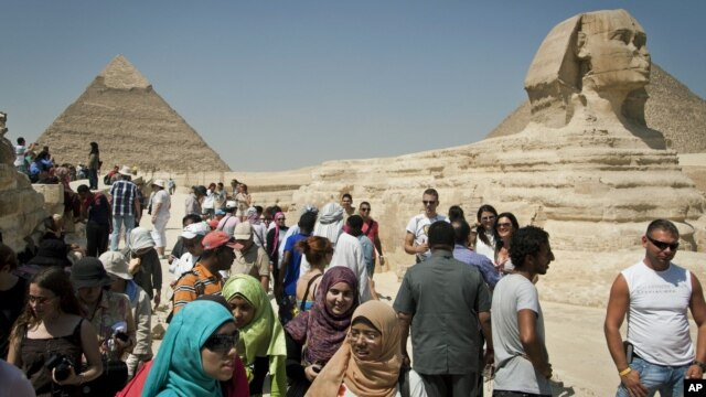 In this September 27, 2012 photo, foreign tourists visit the historical site of the Giza Pyramids, near Cairo, Egypt.