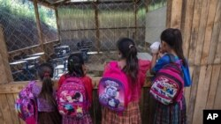 Students wait for their instructor as they look into their classroom flooded the night before by a heavy rain, in the makeshift settlement Nuevo Queja, Guatemala, Tuesday, July 6, 2021. (AP Photo/Rodrigo Abd)
