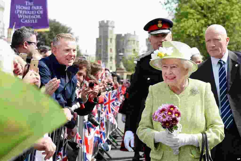 英国女王伊丽莎白二世在伯克郡的温莎城堡在庆祝她的90岁生日的游行时与人们见面。