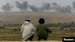 افغانستان میں دو سابق فوجی لڑائی کے بعد علاقے سے دھویں کے بادل اٹھتے دیکھ رہے ہیں۔ فائل فوٹو رائٹرز
