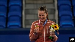 Belinda Bencic of Switzerland looks at her gold medal in the women's singles of the tennis competition at the 2020 Summer Olympics, July 31, 2021, in Tokyo, Japan.