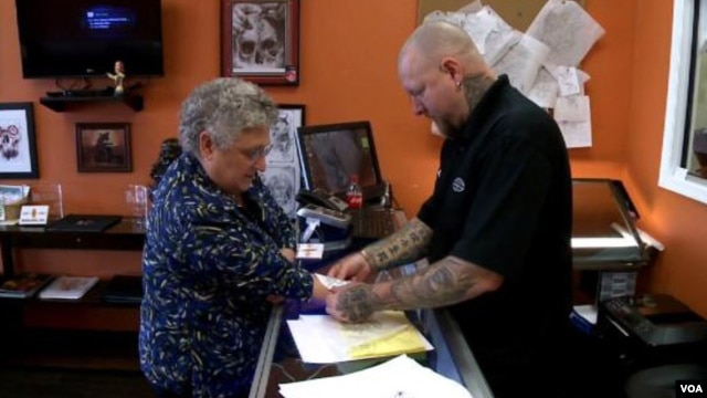 Robin Rhoderick discusses getting a medical tattoo with Jeffery Grimet, owner of Inner Soul Ink, a tattoo salon in Mount Airy, Maryland. (VOA/A. Greenbaum)
