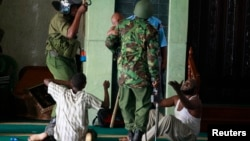 Muslim men are detained by police officers at the Masjid Mussa Mosque in the coastal town of Mombasa, Feb. 2, 2014.