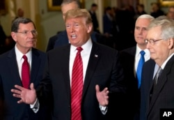 President Donald Trump, accompanied by Vice President Mike Pence, second right, and Senate Majority Leader Mitch McConnell, right, talks to the media after a Senate Republican policy lunch on Capitol Hill, in Washington, Jan. 9, 2019.