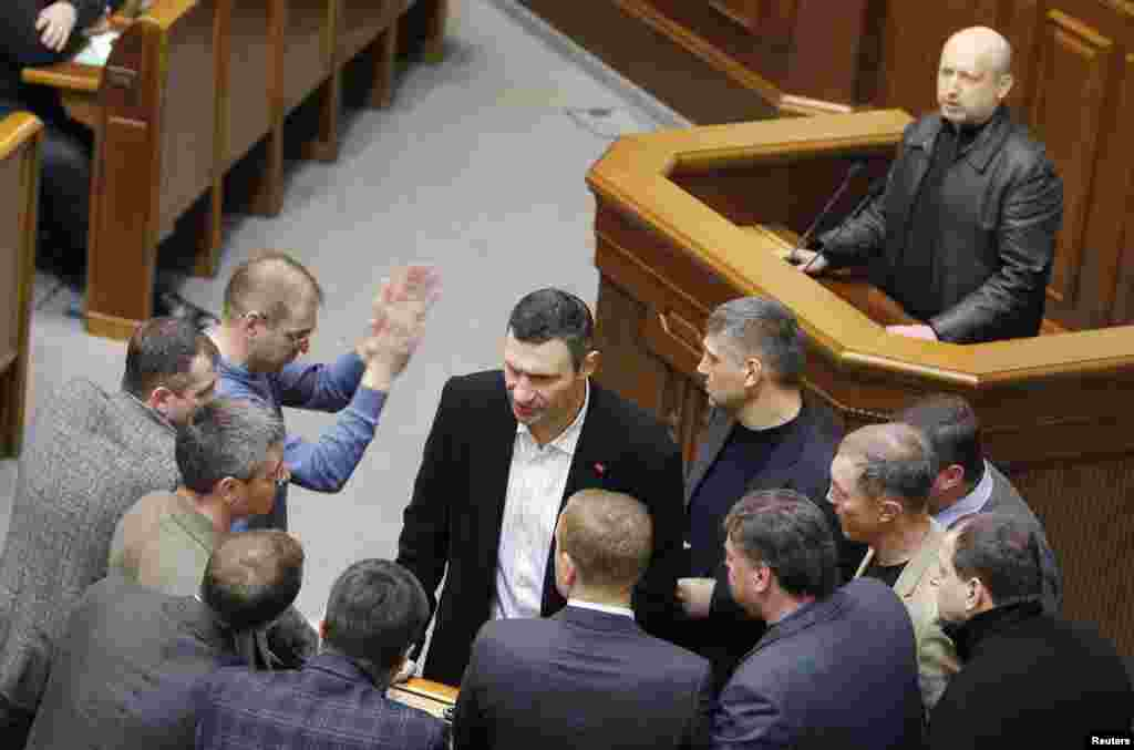 Ukrainian opposition leader and head of the UDAR (Punch) party Vitaly Klitschko (C, front) talks to his colleagues, with newly elected speaker of parliament Oleksander Turchynov (R, top) seen in the background, during a session of the parliament in Kyiv.