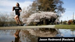 seorang wanita berlari-lari di sekitar Green Lake Park sebagai upaya jarak sosial terus membantu memperlambat penyebaran Covid-19 di Seattle, Washington, AS 29 Maret 2020. (Foto: REUTERS/Jason Redmond)