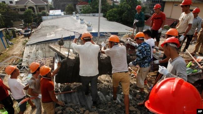 Socorristas intentan retirar escombros el domingo 23 de junio de 2019 en busca de víctimas tras el derrumbe el día anterior de un edificio en construcción en Sihanoukville, Camboya. (AP Foto/Heng Sinith)