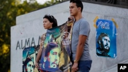 Students stand at attention holding images of Fidel Castro at the university where Castro studied law as a young man, during a vigil in Havana, Cuba, Nov. 27, 2016.